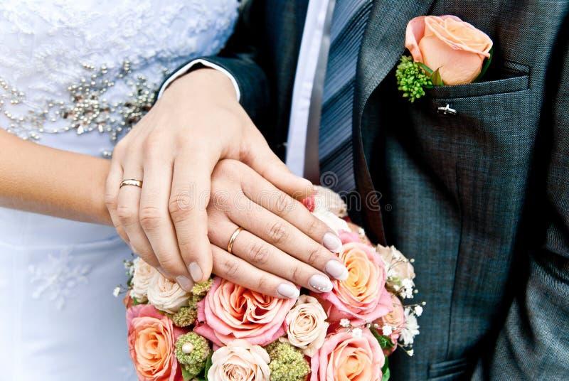 Manos de la novia y del novio imagen de archivo