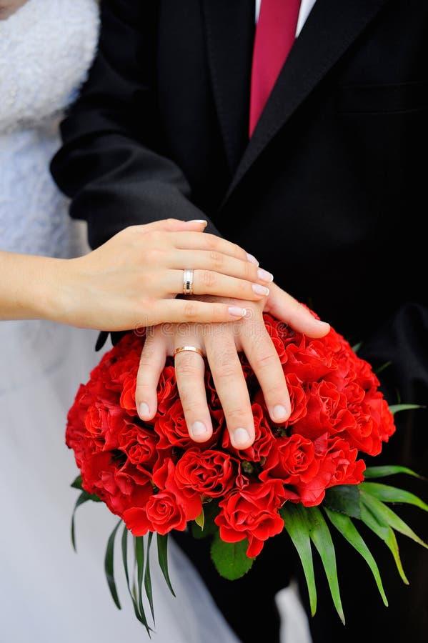 Manos de la novia y del novio, anillos en ramo de la boda fotos de archivo libres de regalías