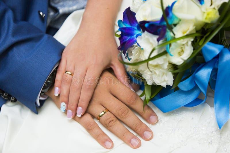 Manos de la novia y del novio con los anillos de bodas de oro y el ramo azul y blanco de la boda fotografía de archivo libre de regalías