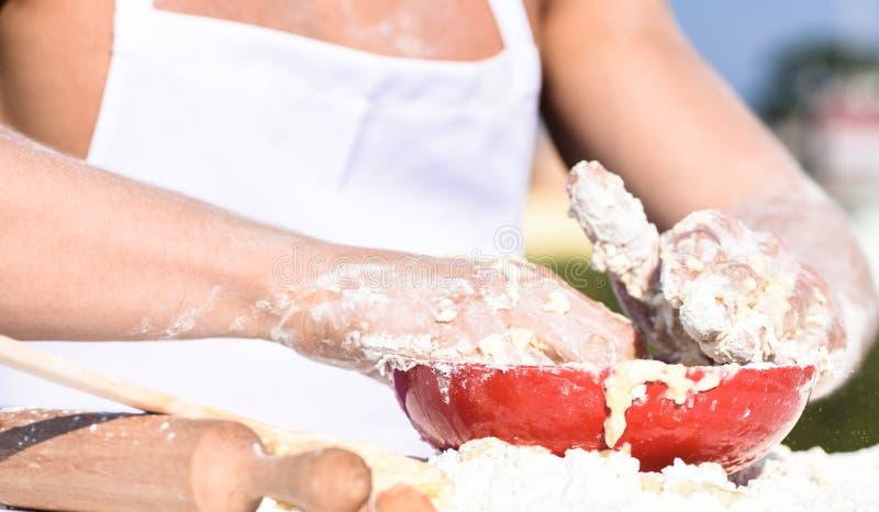 Manos de la pasta de amasamiento muscular del panadero o del cocinero en cuenco Las manos del cocinero cocinan el trabajo con pas imagen de archivo