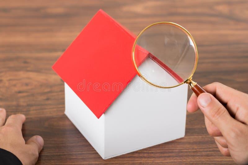 Manos de la persona con la casa de la lupa y del modelo imagenes de archivo