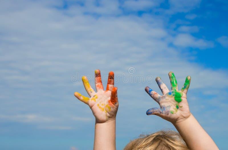 Manos de la pintura del bebé contra el cielo azul imagen de archivo libre de regalías