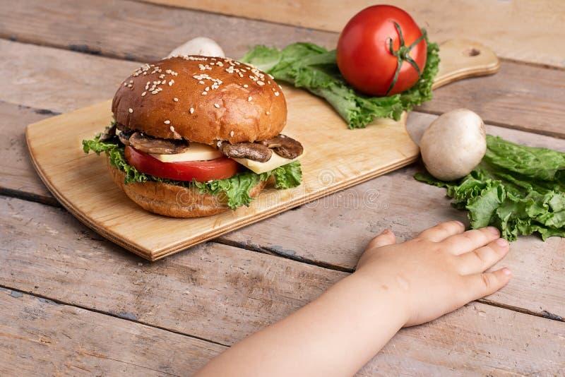 Manos de las muchachas cerca de la hamburguesa de la seta con el queso y tomates, champi?ones crudos y lechuga, tajadera imagen de archivo libre de regalías