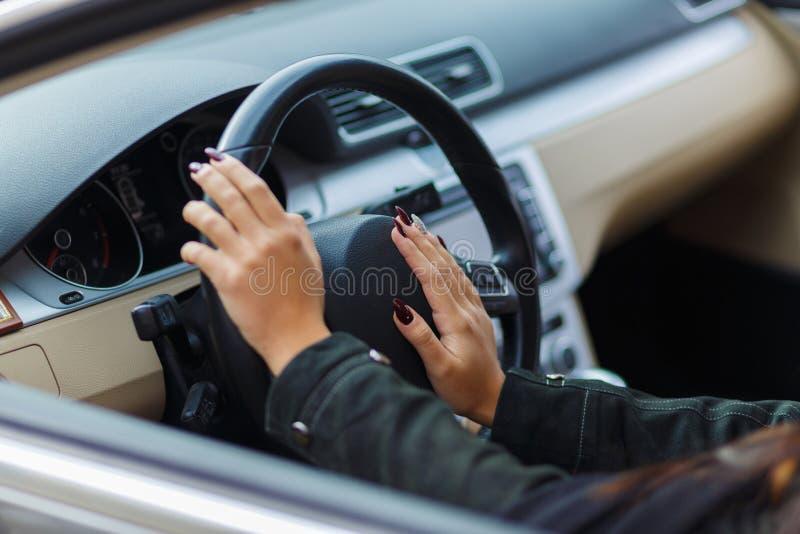 Manos de las muchachas en el volante fotografía de archivo libre de regalías