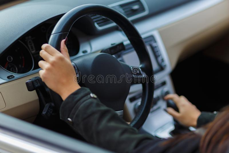 Manos de las muchachas en el volante foto de archivo