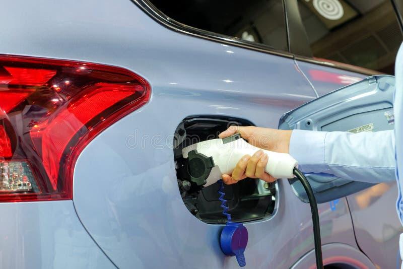 Manos de las mujeres de Asia del primer que están aprovisionando de combustible una nueva electrificación del vehículo imagen de archivo libre de regalías
