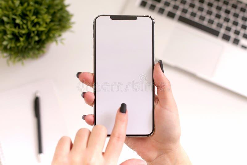 Manos de las mujeres que sostienen el teléfono blanco con la pantalla aislada sobre la tabla con el ordenador foto de archivo libre de regalías