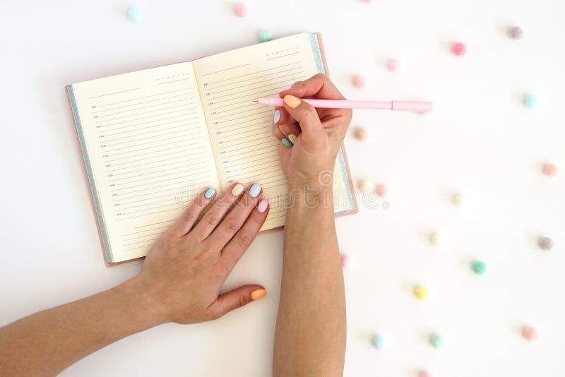 Manos de las mujeres s con la pluma en el cuaderno de notas y las bolas coloridas en la tabla Manicura femenina del color de moda imagenes de archivo