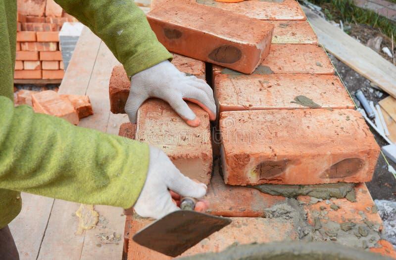Manos de los albañiles en levantamiento de muros de los guantes de la albañilería en emplazamiento de la obra de la casa Levantam imagen de archivo
