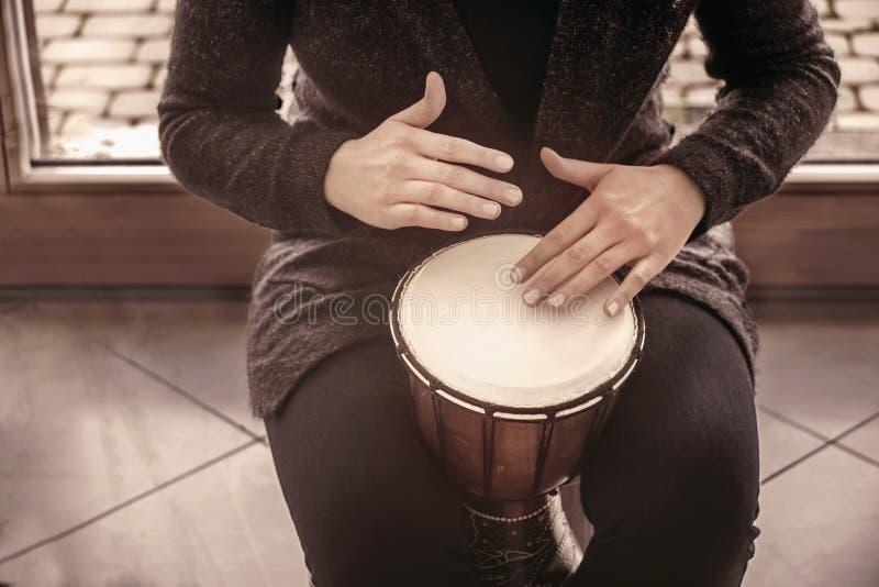Manos de los baterías de la muchacha que juegan el bongo de la percusión foto de archivo