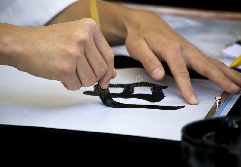 Manos de los calígrafos fotos de archivo