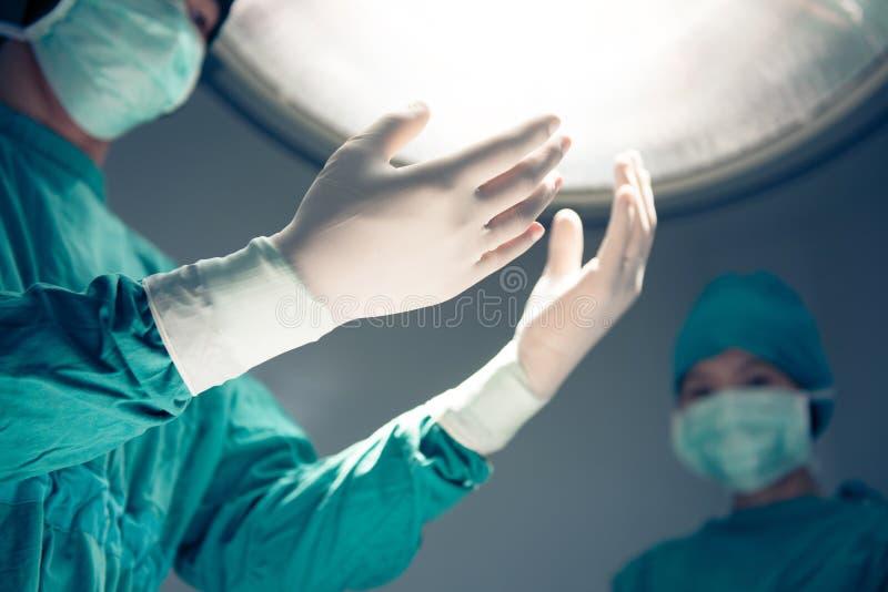 Manos de los cirujanos y luces quirúrgicas en la sala de operaciones imágenes de archivo libres de regalías