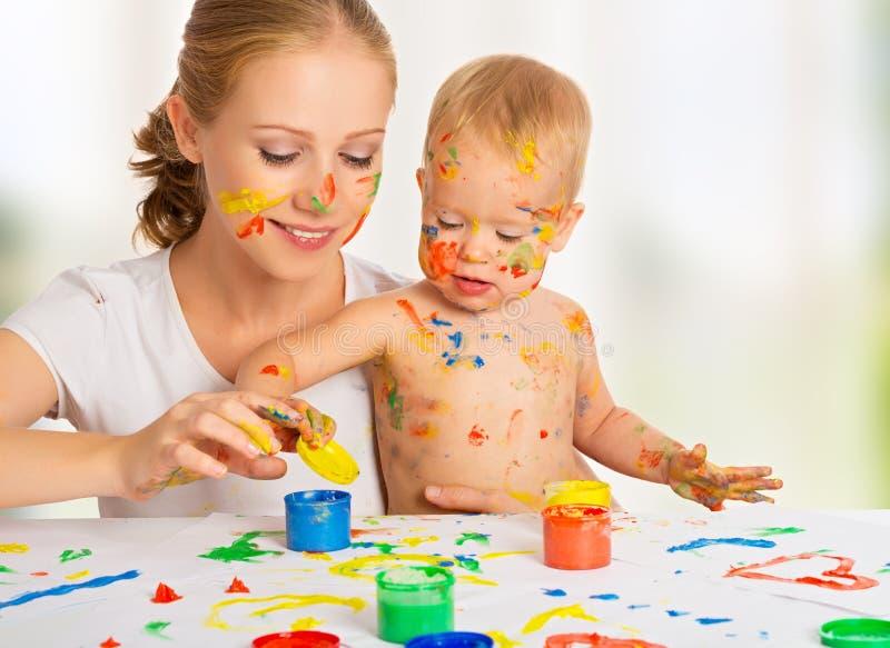 Manos de los colores de la pintura de la madre y del bebé sucias fotografía de archivo