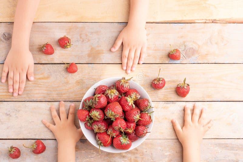 Manos de los niños cerca del cuenco blanco con las fresas, visión superior imagen de archivo libre de regalías