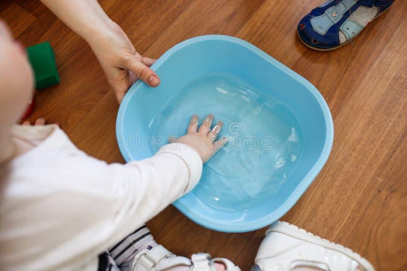 Manos de los niños en un lavabo azul en el piso imágenes de archivo libres de regalías