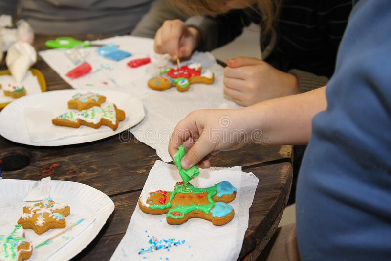 Manos de los niños que fabrican la zanahoria de la Navidad imagen de archivo