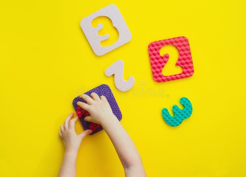 Manos de los niños que juegan con forma de los rompecabezas en gran número en fondo amarillo fotografía de archivo
