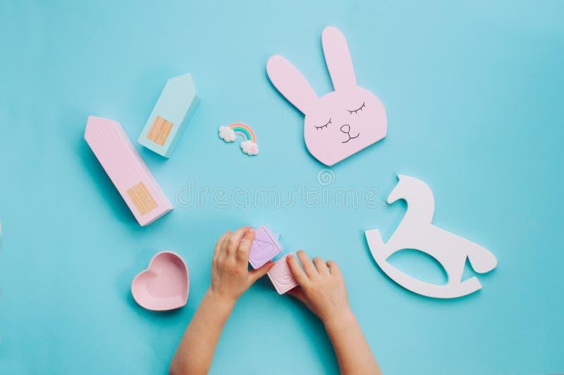 Manos de los niños que juegan con los juguetes en fondo azul foto de archivo