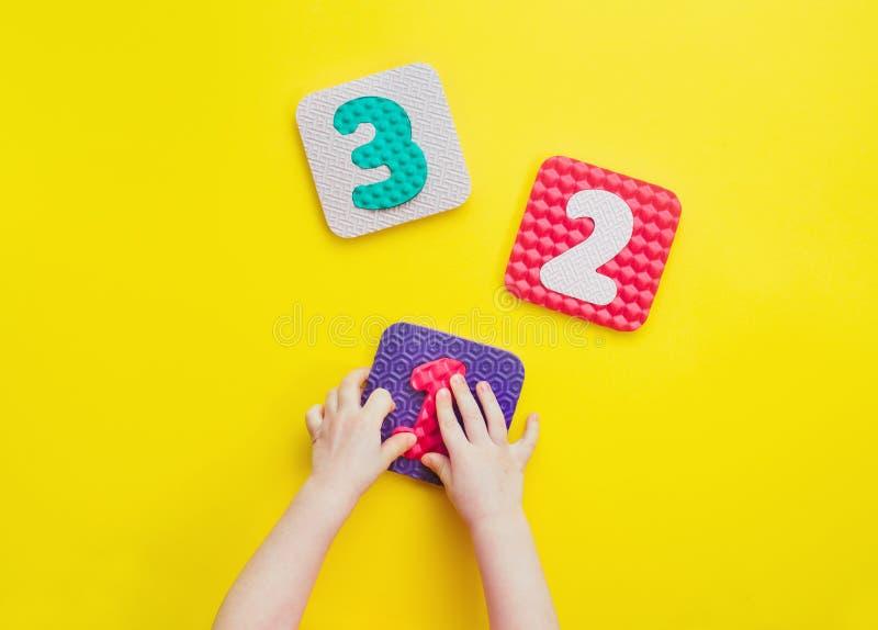 Manos de los niños que juegan con rompecabezas en una forma del número en fondo amarillo imagenes de archivo