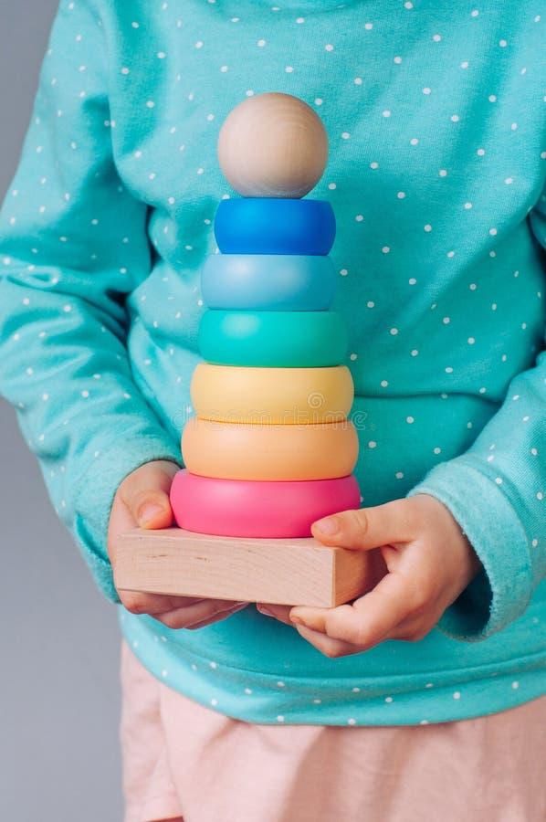 Manos de los niños que sostienen un juguete de la pirámide imágenes de archivo libres de regalías