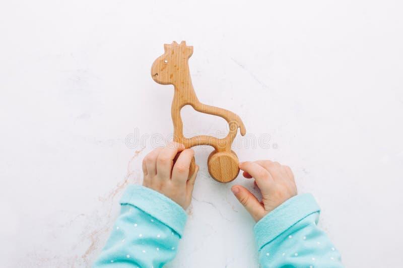 Manos de los niños que sostienen una jirafa de madera del juguete imagenes de archivo