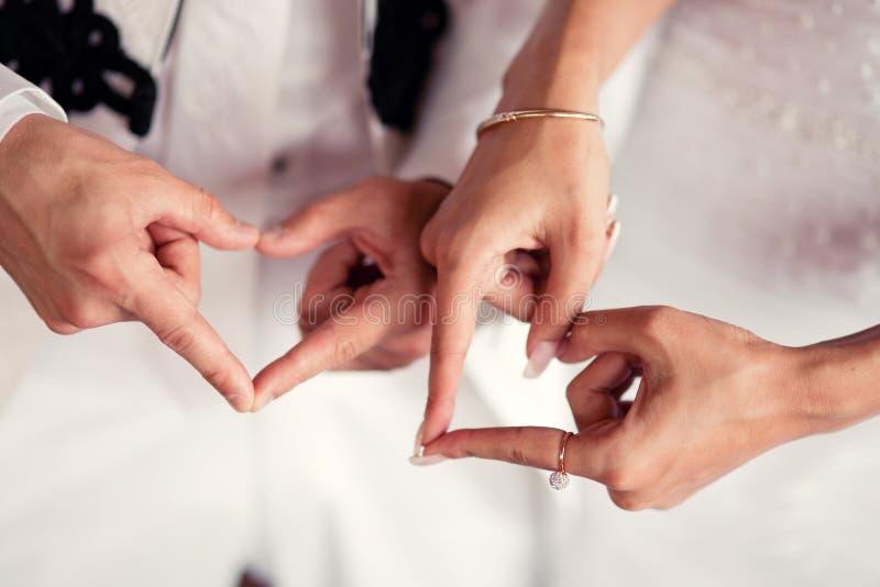 Manos de los pares de la boda y dedos en forma de corazón imagenes de archivo