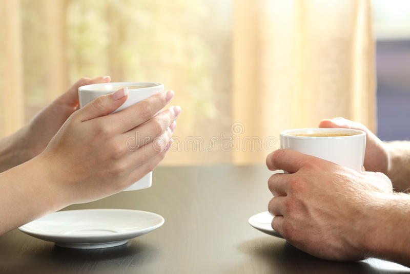 Manos de los pares o de los amigos que sostienen las tazas de café imagenes de archivo