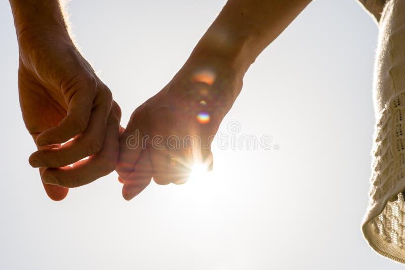 Manos de los pares que se ligan con los rayos de Sun fotografía de archivo libre de regalías