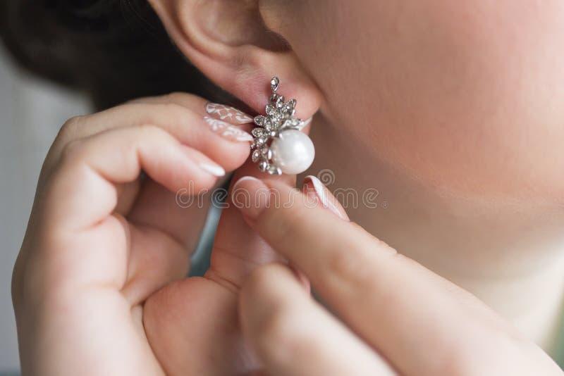 Manos de los pendientes de la perla de la muchacha que llevan imagen de archivo