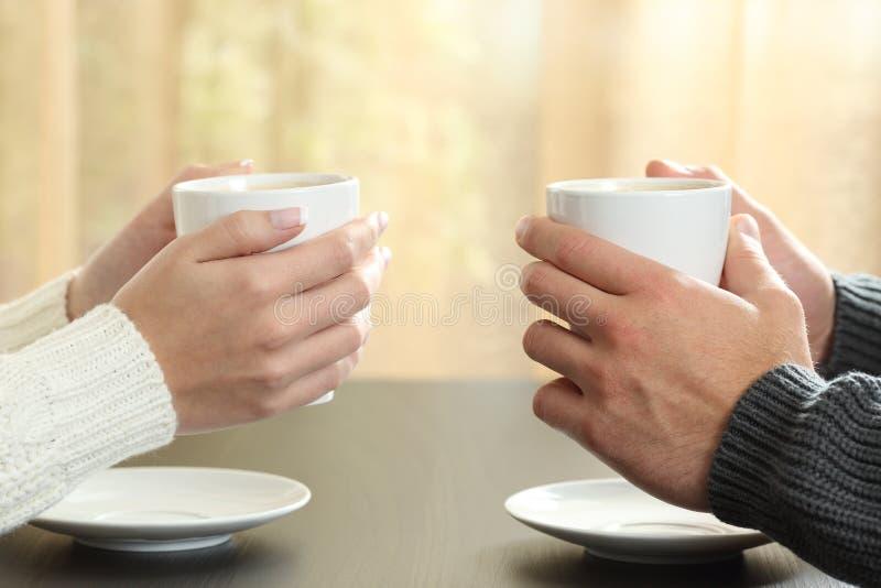 Manos de pares con las tazas de café imagen de archivo