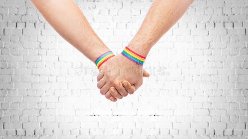 Manos de pares con pulseras del arco iris del orgullo gay imagenes de archivo