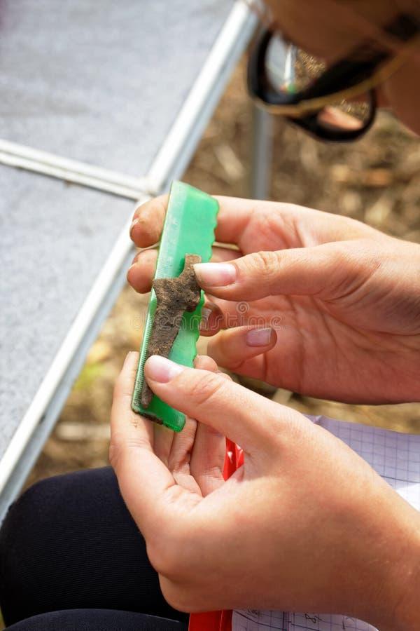Manos de un arqueólogo que mide con una punta de flecha medieval de la regla imagenes de archivo