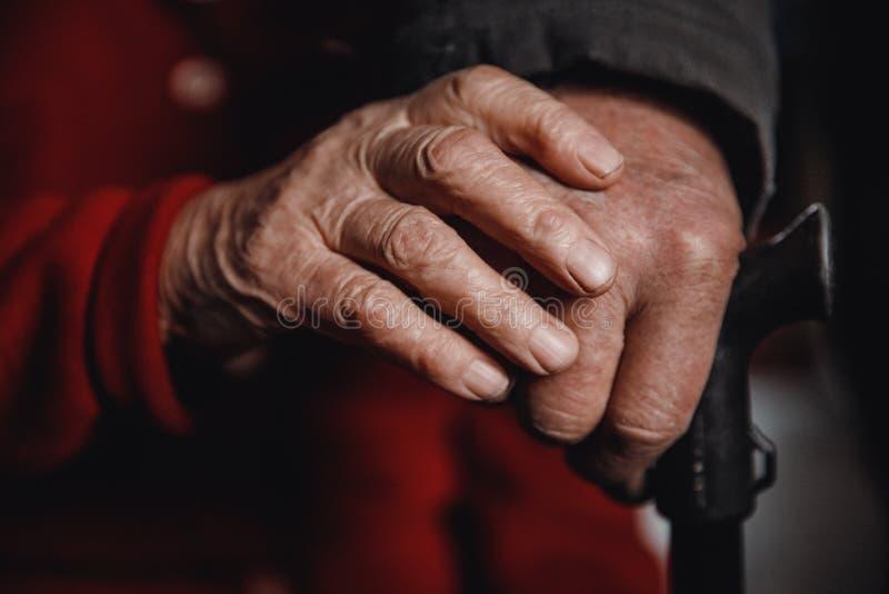 Manos de un bastón de la tenencia de la mujer mayor y del hombre, piel arrugada fotos de archivo libres de regalías