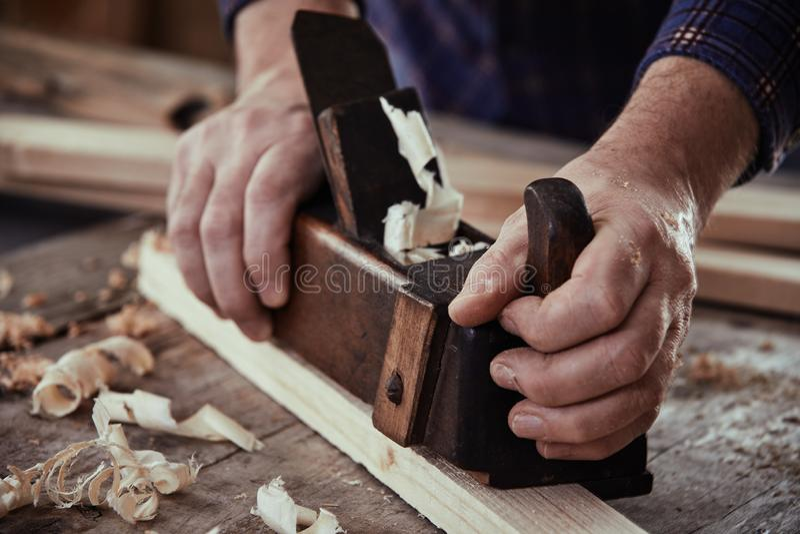 Manos de un carpintero que usa un avión del vintage foto de archivo libre de regalías