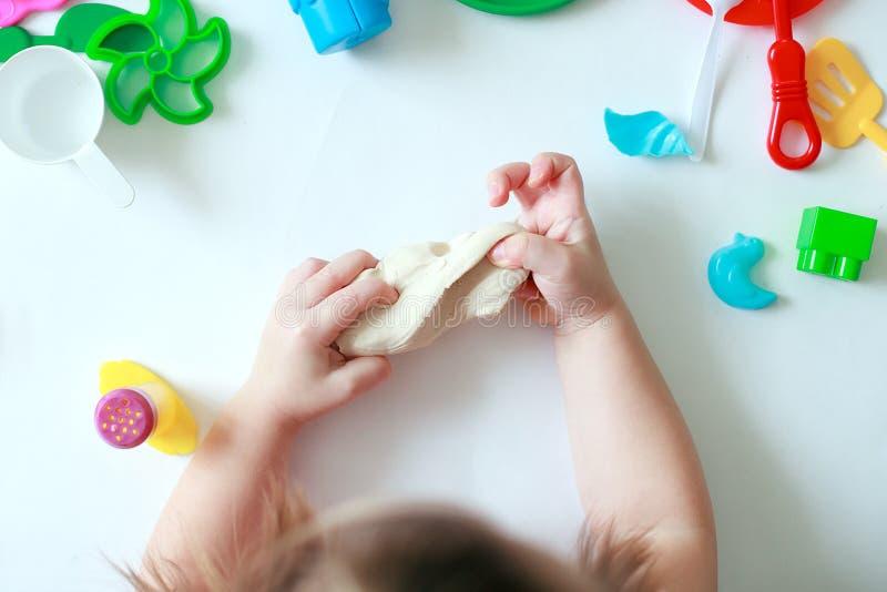 Manos de un Childs que sostienen la pasta del juego Concepto de educación y de terapia sensetive de niños, visión superior fotos de archivo