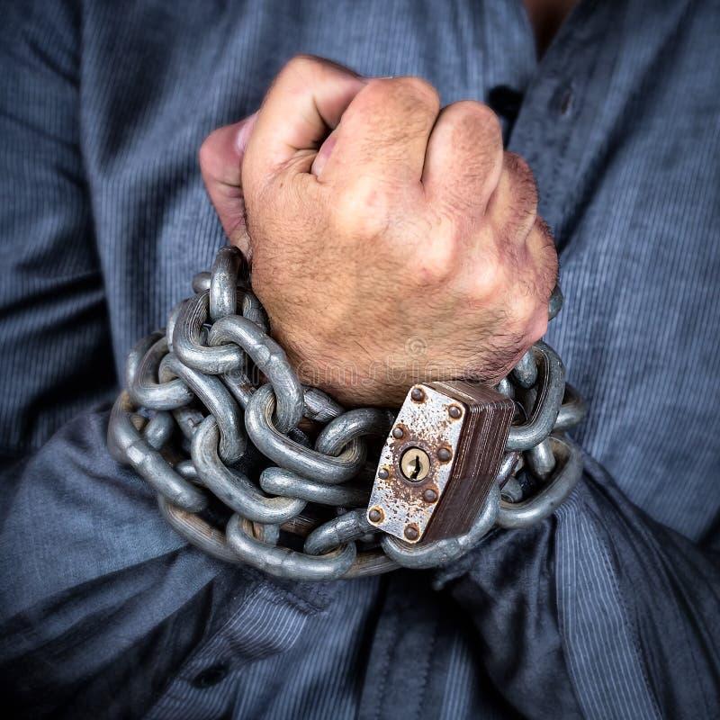 Manos de un hombre formalmente vestido encadenado con una cadena del hierro y una a foto de archivo