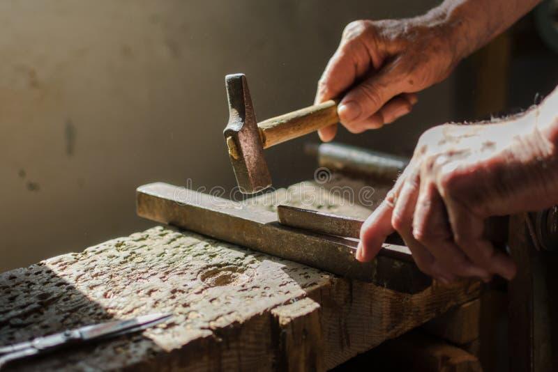 Manos de un hombre mayor que trabaja en el hierro con el martillo imagen de archivo libre de regalías