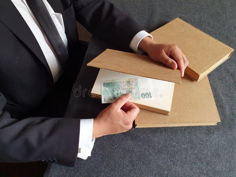 manos de un hombre de negocios con dinero checo y libros sobre la mesa fotografía de archivo