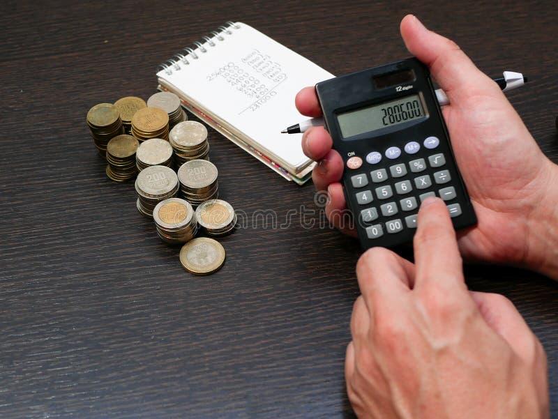Manos de un hombre usando una calculadora solar para contar monedas de la moneda de los Pesos colombianos con una pluma en su man foto de archivo libre de regalías