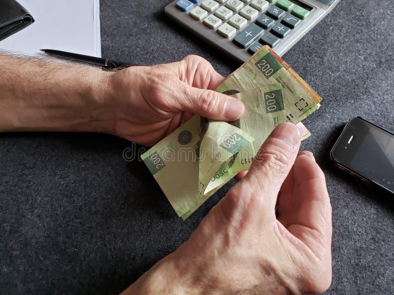 manos de un m?s viejo hombre que cuenta billetes de banco mexicanos imagen de archivo
