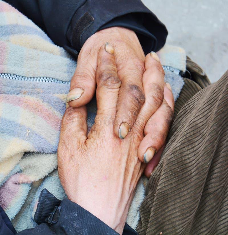 Manos de un mendigo en rezo, en la calle, cierre para arriba imagenes de archivo