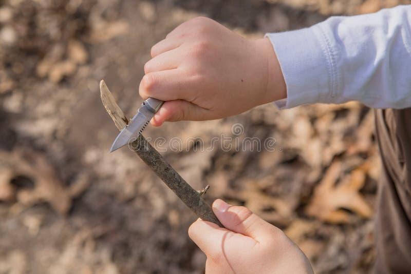 Manos de un muchacho joven que corta un pedazo de madera imagen de archivo libre de regalías