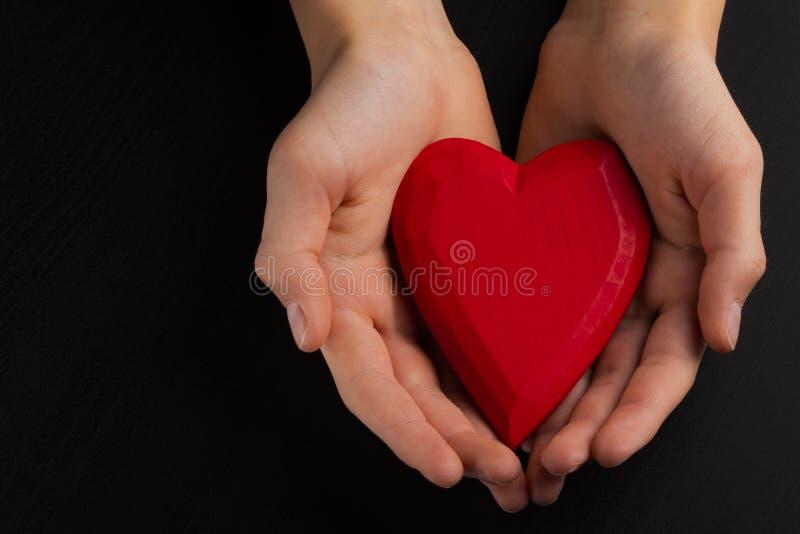 Manos de un niño del adolescente que lleva a cabo un corazón de madera rojo en sus manos fotos de archivo libres de regalías