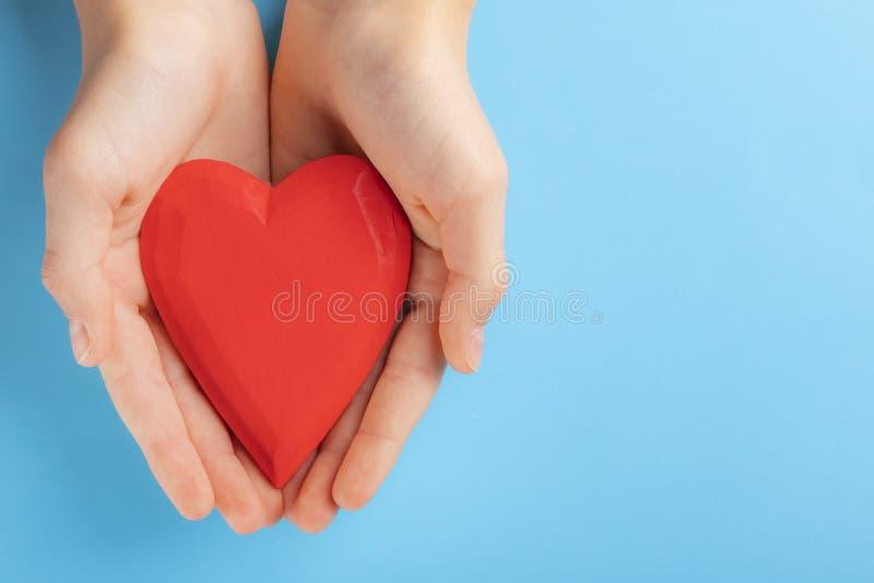 Manos de un niño del adolescente que lleva a cabo un corazón de madera rojo en sus manos Fondo para una tarjeta de la invitación  imagen de archivo