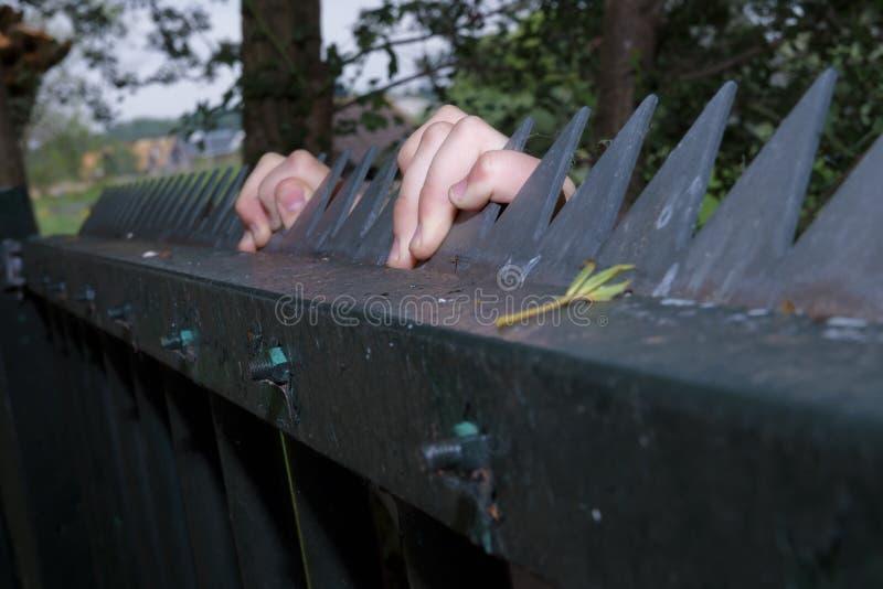 Manos de un niño del refugiado en un fence1 de acero foto de archivo