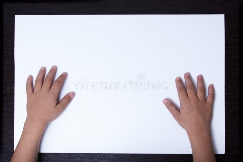 Manos de un niño en una hoja de papel blanca imágenes de archivo libres de regalías