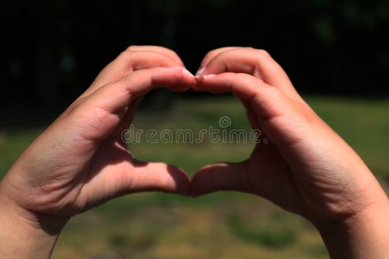 Manos de un niño que hace forma del corazón imagenes de archivo