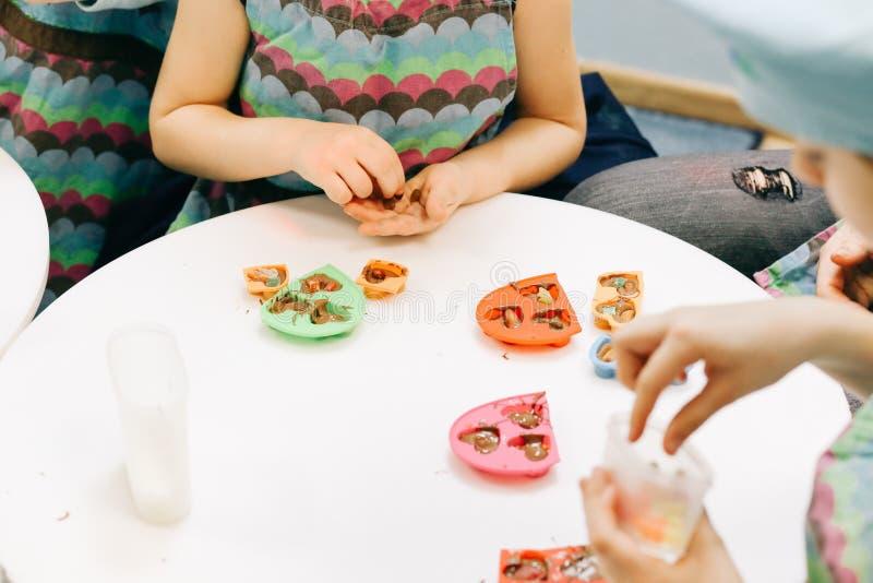 Manos de un niño, de una clase principal en cocinar el chocolate, de la fruta plegable y del chocolate en moldes fotos de archivo libres de regalías