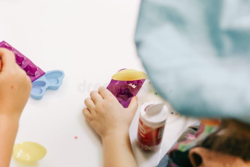 Manos de un niño, de una clase principal en cocinar el chocolate, de la fruta plegable y del chocolate en moldes foto de archivo libre de regalías