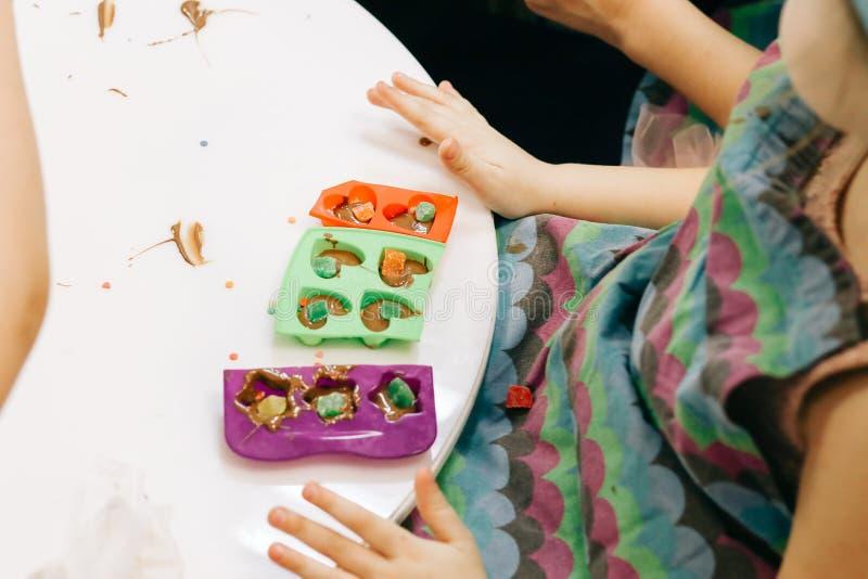 Manos de un niño, de una clase principal en cocinar el chocolate, de la fruta plegable y del chocolate en moldes imagen de archivo